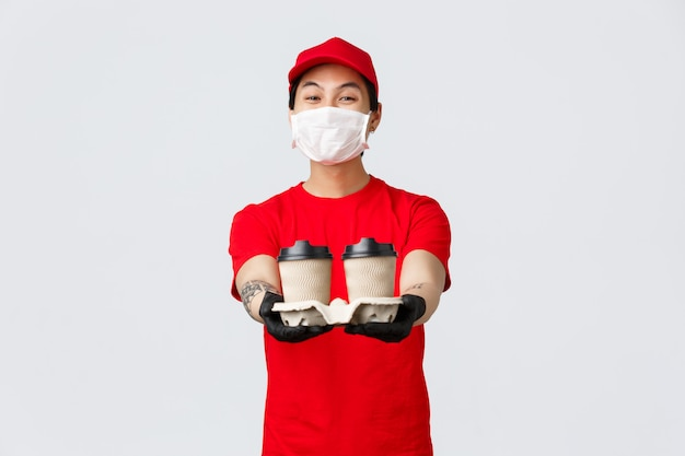 Przyjazny azjatycki mężczyzna dostawy podczas pandemii covida 19, przynieś zamówienie na jedzenie, wyciągnij ręce z kawą z lokalnej kawiarni, którą zamówiłeś lub przez internet
