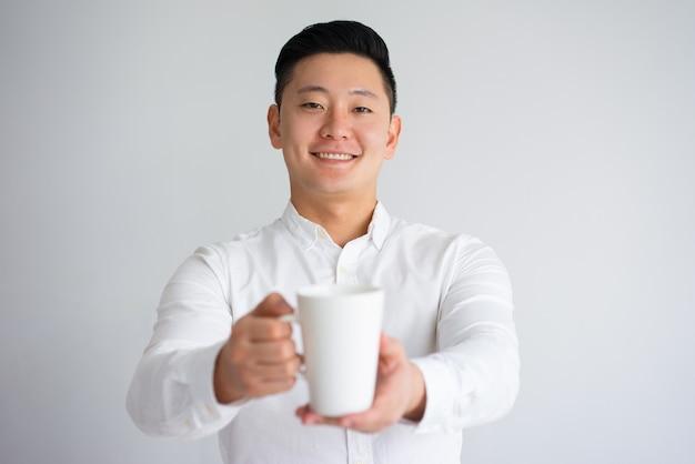 Przyjazny azjatycki młody człowiek oferujący kawy