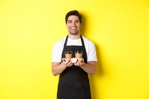 Przyjazny barista w czarnym fartuchu podaje zamówienie na wynos, trzymając dwie filiżanki kawy i uśmiechnięty, stojąc na żółtym tle.