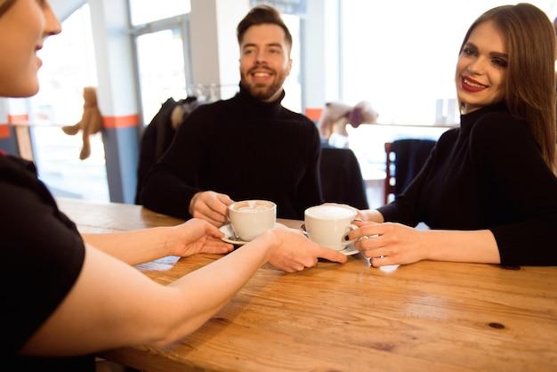 Przyjazny barman serwujący klientom kawę espresso we wnętrzu nowoczesnej kawiarni.