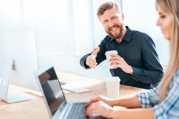 Przyjazny biznesmen siedzi przy biurku i wyciąga rękę do uścisku dłoni