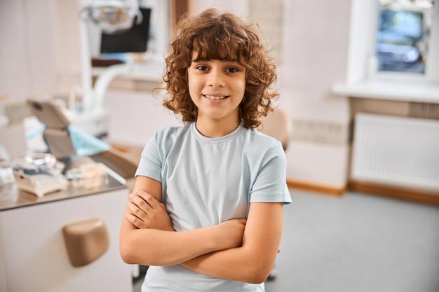 Przyjazny brunetka chłopiec uśmiechający się z rękami skrzyżowanymi na piersi i pozujący w gabinecie dentystycznym
