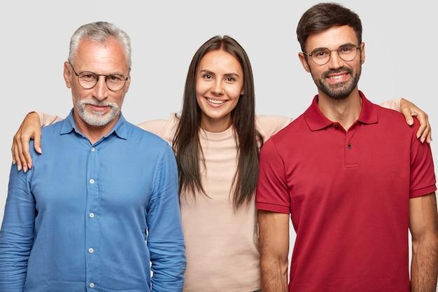 Przyjazny dziadek, wnuczka i wnuk stoją blisko i obejmują się