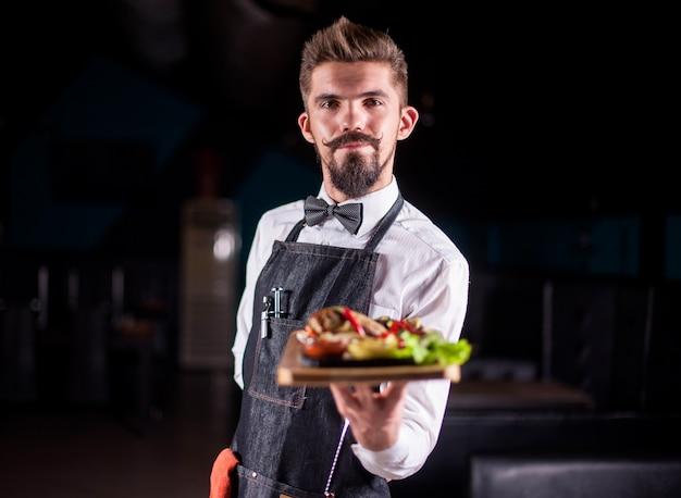 Przyjazny flunky pomocnie trzyma ugotowane danie w restauracji.