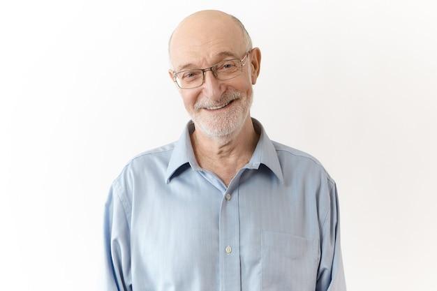 Przyjazny humorystyczny dziadek z białą brodą uśmiecha się radośnie do kamery. elegancki schludny starszy biznesmen w okularach, ciesząc się z udanych skutecznych wyników pracy, pozowanie na białym tle w studio