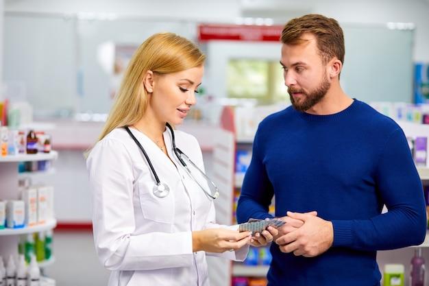 Przyjazny kaukaski farmaceuta przeprowadza miłą rozmowę z klientem