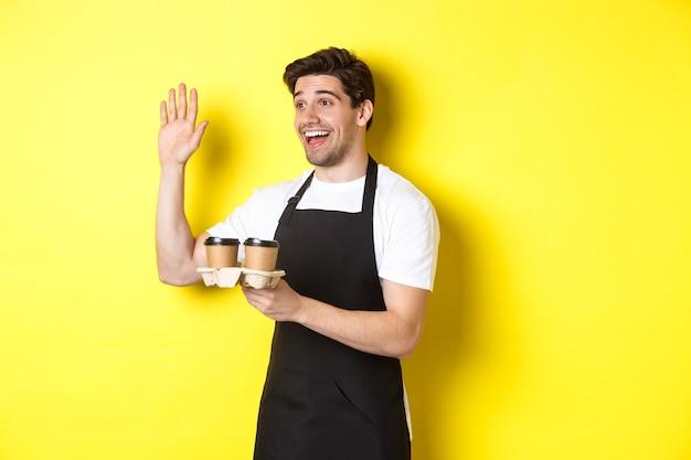 Przyjazny kelner w kawiarni macha ręką do klienta, trzymając kawę na wynos, stojąc przed żółtą ścianą w czarnym fartuchu.