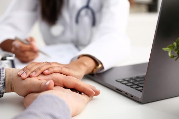 Przyjazny kobiece kobieta lekarz trzymać rękę mężczyzny pacjenta