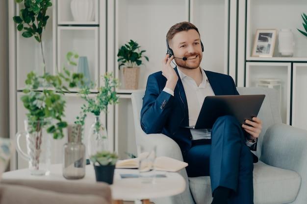 Przyjazny konsultant biznesowy lub kierownik sprzedaży w garniturze za pomocą zestawu słuchawkowego laptopa i rozmawiając o komunikacji wideo z klientem, siedząc w salonie w wygodnym fotelu. ludzie biznesu w pracy