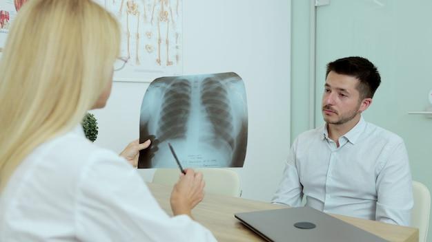 Przyjazny lekarz kobieta daje dobre wieści x-ray płuc pacjenta pacjenta w szpitalu kryty. opieka zdrowotna, koncepcja obsługi personelu medycznego i lekarza.