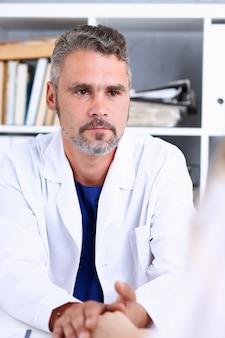 Przyjazny lekarz mężczyzna trzymać ramię kobiety w biurze