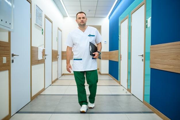 Przyjazny lekarz mężczyzna w mundurze trzyma notebook w korytarzu kliniki. profesjonalny specjalista medyczny w szpitalu, laryngolog lub otolaryngolog, ginekolog lub mammolog, chirurg