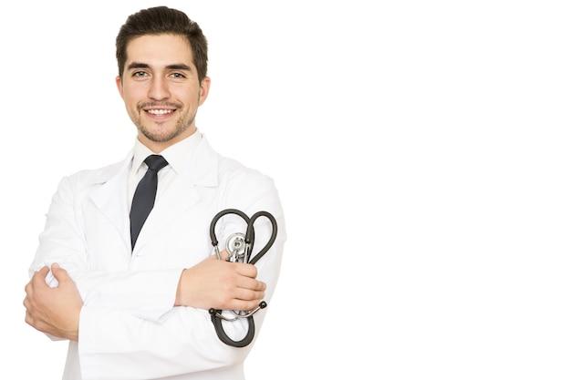 Przyjazny lekarz. portret przystojny szczęśliwy lekarz trzymając stetoskop uśmiechnięty na biel