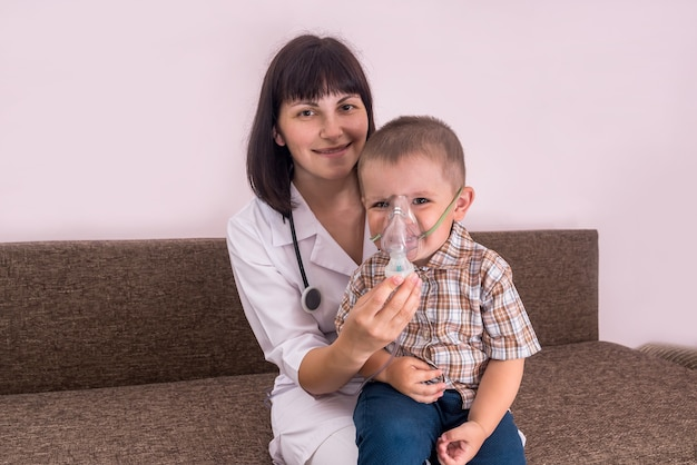 Przyjazny lekarz robi inhalację chłopcu za pomocą nebulizatora