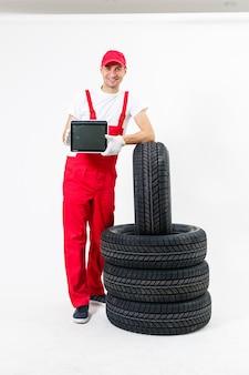 Przyjazny mechanik samochodowy z oponami i kluczem