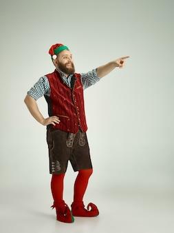 Przyjazny mężczyzna ubrany jak zabawny gnom pozujący na odosobnionej szarości