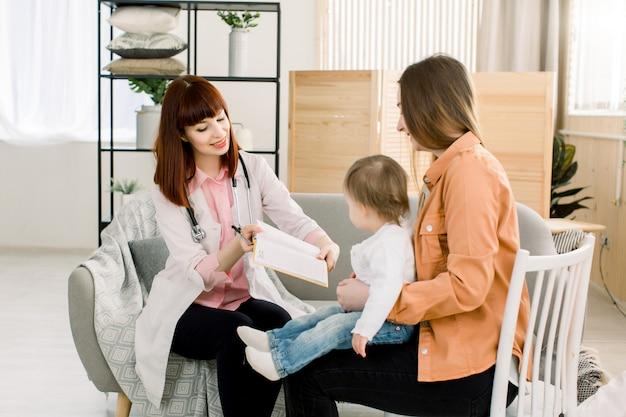 Przyjazny młoda kobieta lekarz pediatra rozmawia z matką dziewczynki po badaniu