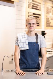 Przyjazny młody blond męski barista z ręcznikiem na ramieniu stojący przy miejscu pracy przed kamerą i patrząc na ciebie