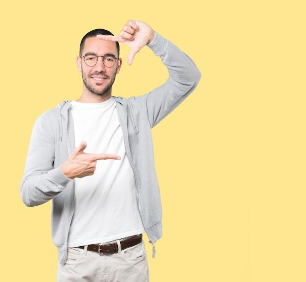 Przyjazny młody człowiek robi gest robienia zdjęcia rękami