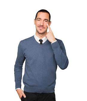 Przyjazny młody człowiek robi gest uważności z ręką wskazującą na jego oko