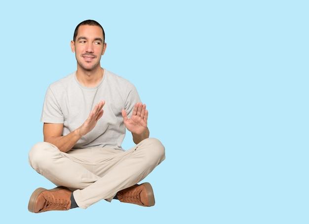 Przyjazny młody człowiek robi gest zachować spokój