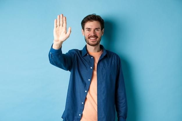 Przyjazny młody człowiek uśmiechając się i podnosząc rękę do przybicia piątki, rezygnując z przywitania się lub przywitania, stojąc na niebieskim tle.