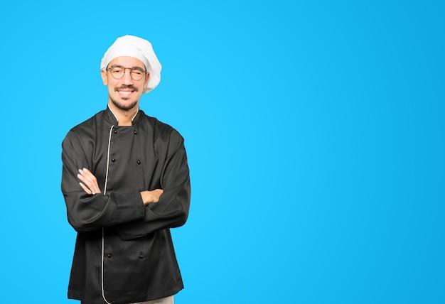 Przyjazny młody szef kuchni mruga okiem
