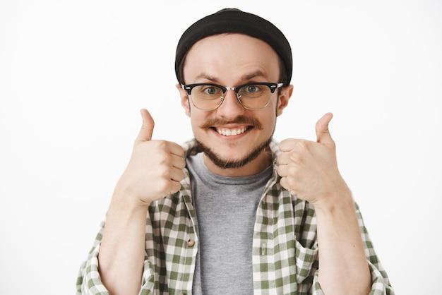 Przyjazny, optymistyczny i szczęśliwy, przystojny mężczyzna z brodą i wąsami w czarnej czapce i przezroczystych okularach uśmiechnięty radośnie, pokazujący kciuki w górę w aprobacie lub podobnym geście