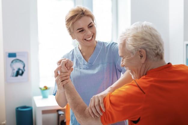 Przyjazny personel. radosna, pozytywna pielęgniarka uśmiechająca się do pacjenta podczas wykonywania zabiegu