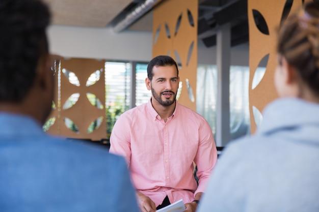 Przyjazny, pewny siebie trener biznesu przemawiający przed publicznością