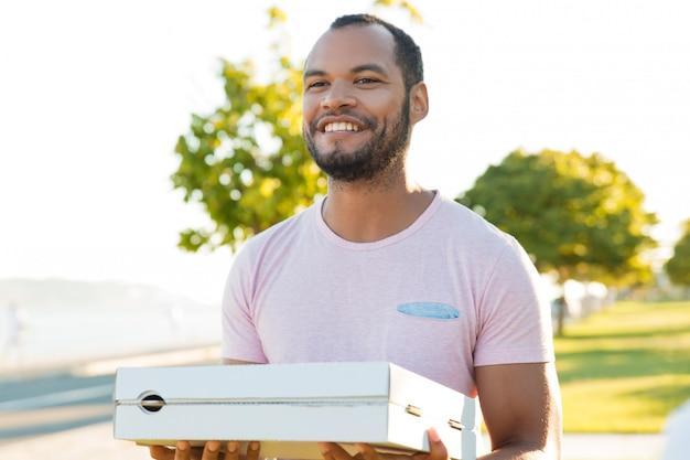 Przyjazny podekscytowany przystojny facet dostarczający pizzę
