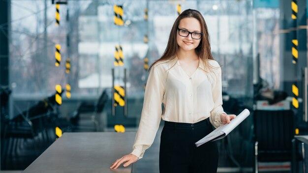 Przyjazny pracownik. młody uśmiechający się stażysta w okularach trzymając schowek z dokumentami stoją w miejscu pracy.