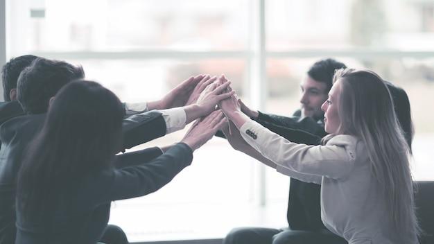 Przyjazny profesjonalny zespół biznesowy zadowolony z jego zwycięskich dłoni splecionych razem