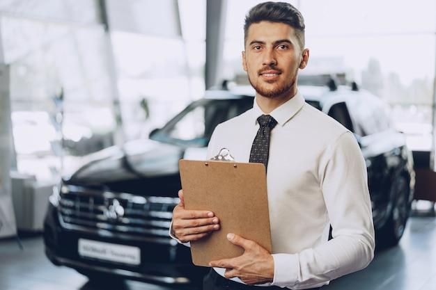Przyjazny Przystojny Mężczyzna Sprzedawca Samochodów Stojący W Salonie Samochodowym Premium Zdjęcia