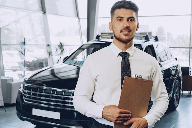 Przyjazny przystojny mężczyzna sprzedawca samochodów stojący w salonie samochodowym