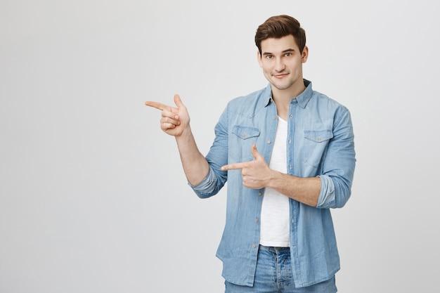 Przyjazny przystojny mężczyzna wskazując palcami po lewej stronie reklamy