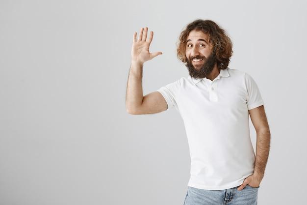 Przyjazny przystojny mężczyzna z bliskiego wschodu mówi cześć, macha ręką w geście pozdrowienia
