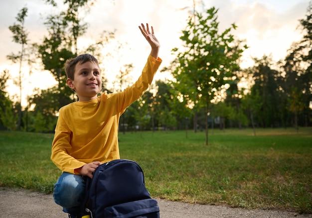 Przyjazny przystojny, sympatyczny, czarujący uczeń 9 lat, siedzi na kolanach na ścieżce w parku, macha ręką obok plecaka, rozgląda się i uśmiecha słodko zębami.