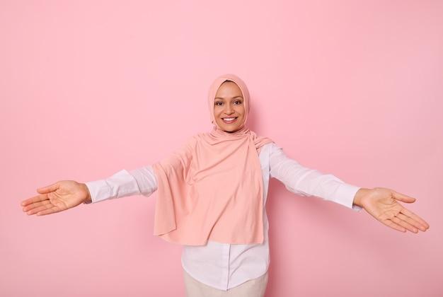 Przyjazny, słodki uśmiech z pięknym, uroczym, ząbkowanym uśmiechem młoda muzułmanka arabka w różowym hidżabie patrząca na kamerę z rozpostartymi ramionami pokazująca gościnność, na kolorowym tle z kopią miejsca