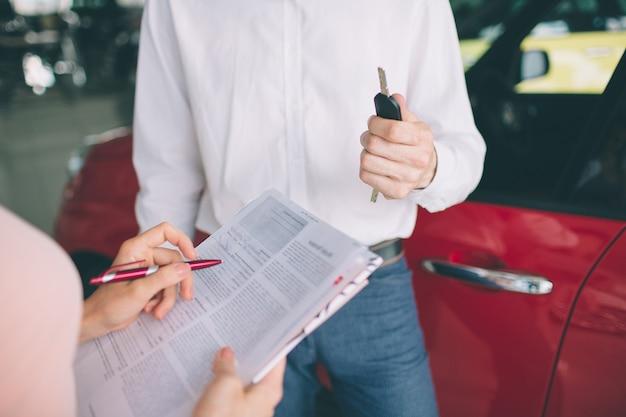 Przyjazny sprzedawca samochodów rozmawia z m?od? kobiet? i pokazuj?c nowy samochód wewn?trz salonu podpisanie umowy.