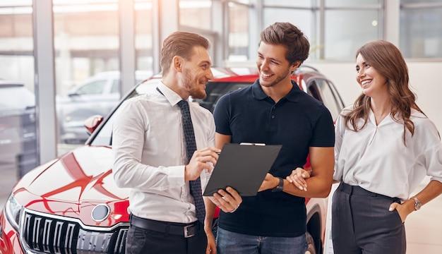 Przyjazny sprzedawca ze schowkiem przedstawiający umowę z szczęśliwym mężczyzną i kobietą podczas sprzedaży pojazdu w salonie samochodowym
