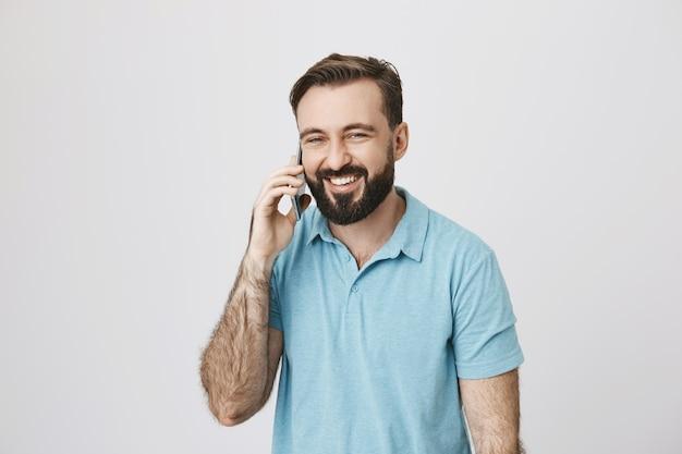 Przyjazny szczęśliwy brodaty facet rozmawia przez telefon, śmiejąc się i uśmiechając