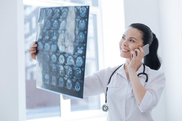 Przyjazny, szczęśliwy i wykwalifikowany onkolog pracujący w klinice podczas omawiania wyniku tomografii komputerowej i korzystania z telefonu
