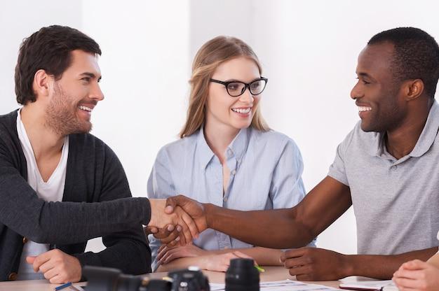 Przyjazny uścisk dłoni. dwóch ludzi biznesu w swobodnym uścisku dłoni, podczas gdy kobieta siedzi między nimi i uśmiecha się