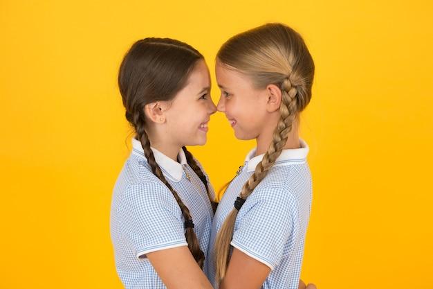 Przyjazny uścisk. słodkie uczennice. dziewczęca pleciona fryzura. wesoły uczennice żółte tło. małe dziewczynki bawiące się ładnymi warkoczami. najlepsi przyjaciele pięknych uczennic. powrót do koncepcji szkoły.