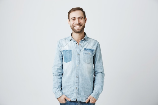 Przyjazny uśmiechnięty brodaty facet stojący w dżinsowej koszuli