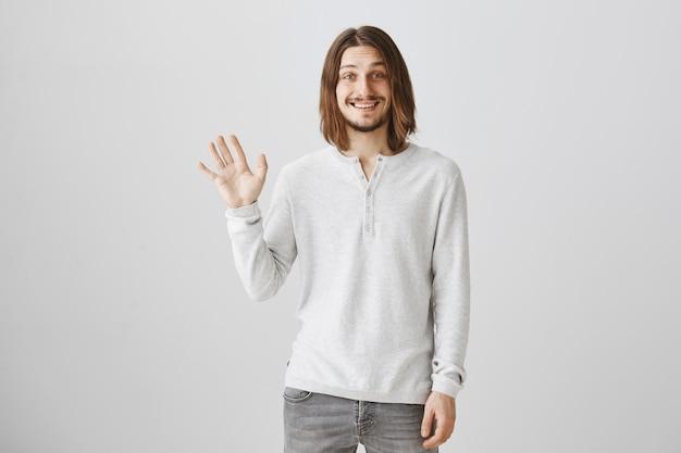 Przyjazny uśmiechnięty facet wita, macha ręką, aby się przywitać
