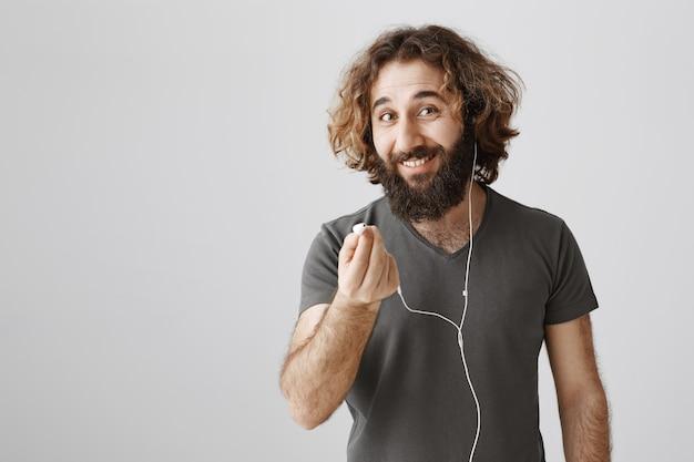 Przyjazny uśmiechnięty facet z bliskiego wschodu sugeruje słuchawki do wspólnego słuchania muzyki