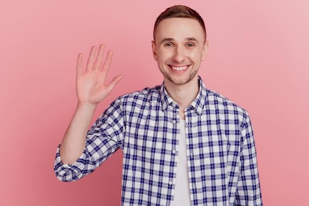 Przyjazny uśmiechnięty mężczyzna machający ręką, aby cię przywitać, wykonaj gest cześć i wygląda na szczęśliwego, widząc cię stojącego na różowym tle