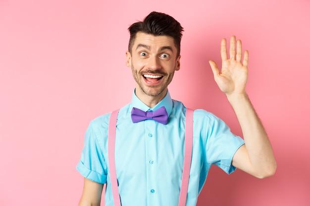 """Przyjazny uśmiechnięty mężczyzna w śmiesznej muszce wita się, macha ręką, by cię przywitać, robi gest """"cześć"""" i wygląda na szczęśliwego yo widzisz, stojącego na różowym tle."""